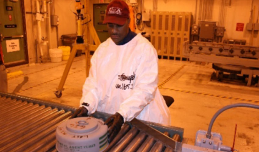 A munitions handler guides the last M23 VX land mine in the Anniston Army Depot stockpile as it moves on the conveyor to the destruction process.